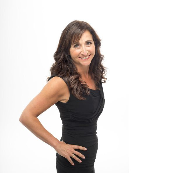 Image or Marli Rusen in black dress with hands on hips. White background.